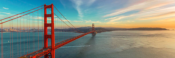 Golden Gate Bridge Photograph of Golden Gate Bridge shortly after sunset. This is panoramic view of Golden Gate. Bridge is brightly illuminated and located on left side of photograph with colorful sunset sky. golden gate bridge stock pictures, royalty-free photos & images