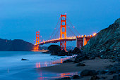 A view of the Golden Gate Bridge in San Francisco, California at night from a beach below with glowing city lights against blue sky and light trails from boats.