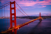 Once in a lifetime Golden Gate Bridge Sunset over San Francisco California blue hour sunset of iconic suspension bridge long exposure time lapse with headlights and traffic crossing the Bay Area bridge