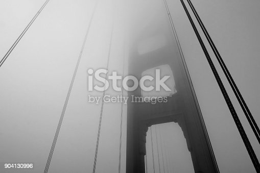 1030949292 istock photo Golden Gate Bridge tower in black and white with fog rolling, San Francisco 904130996