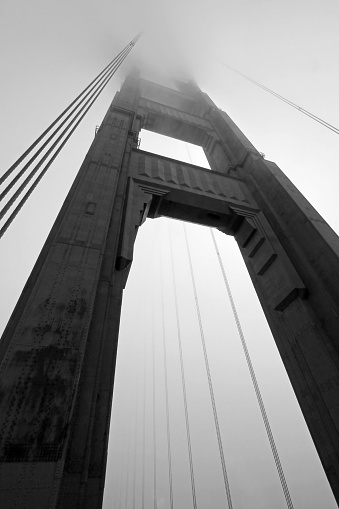 Golden Gate Bridge tower in black and white with fog rolling, San Francisco, USA