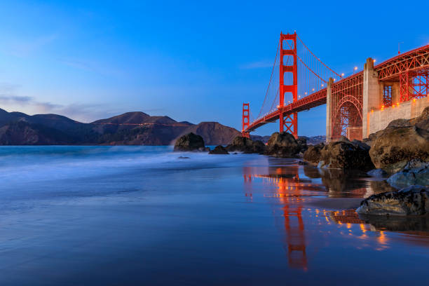 Golden Gate Bridge view from the hidden and secluded rocky Marshall's Beach at sunset in San Francisco, California stock photo