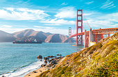Classic view of famous Golden Gate Bridge with cargo ship on a sunny day with blue sky and clouds in summer, San Francisco, California, USA