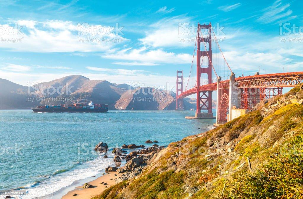 Golden Gate Bridge mit Frachtschiff bei Sonnenuntergang, San Francisco, Kalifornien, USA – Foto