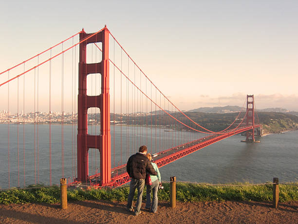 Golden gate Bridge with couple admiring the view. stock photo