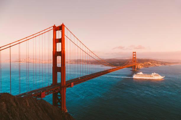 Golden Gate Bridge mit Kreuzfahrtschiff bei Sonnenuntergang, San Francisco, Kalifornien, USA – Foto