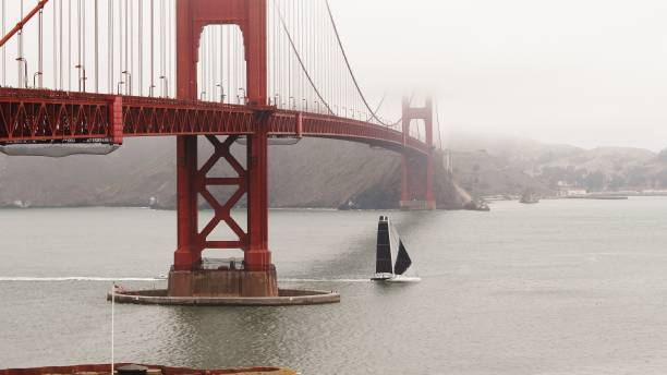 Golden Gate Bridge with Fog and large Sailboat sailing under Golden Gate Bridge with Fog and large Sailboat sailing under san francisco bay stock pictures, royalty-free photos & images