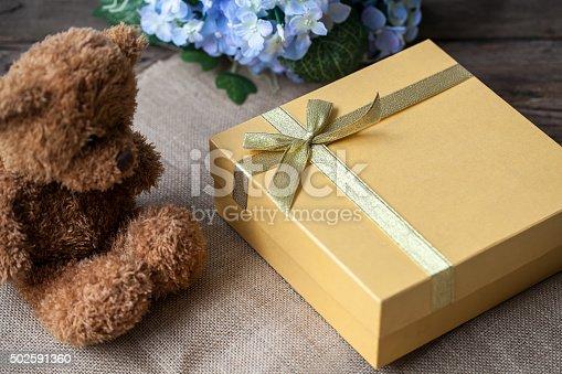 istock Golden gift box and teddy bear 502591360