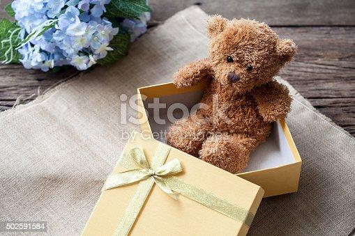 istock Golden gift box and teddy bear 502591584