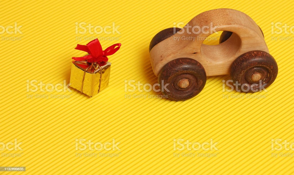 golden gift box with red ribbon in front of wooden car toy on...