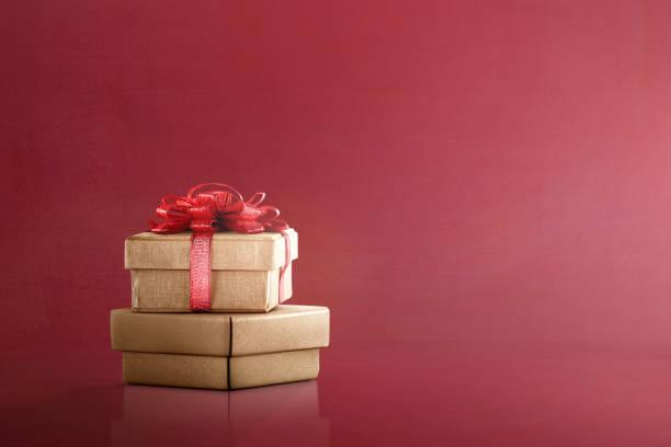 golden geschenkbox mit einem roten band - günstige weihnachtsgeschenke stock-fotos und bilder