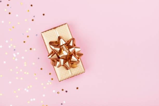 goldenen geschenk oder präsent-box und sternen konfetti auf rosa hintergrund draufsicht. flache laien komposition für geburtstag, weihnachten oder hochzeit. - originelle geburtstagsgeschenke stock-fotos und bilder