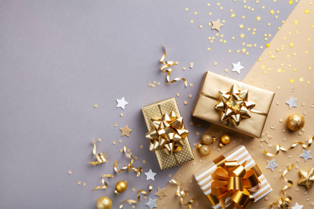 golden gift or present boxes with golden bows and confetti top view and flat lay. christmas background. - regalo natale foto e immagini stock