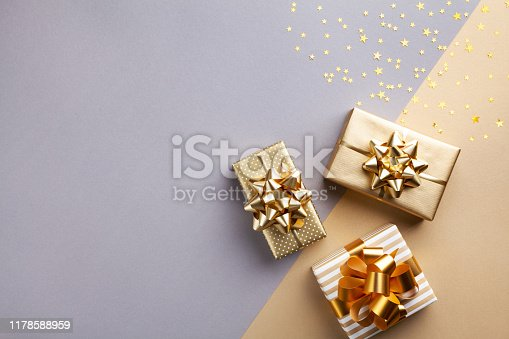 Golden gift or present boxes with golden bows and star confetti top view. Christmas background. Flat lay style.