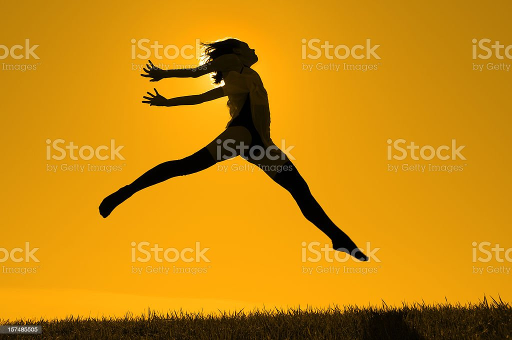Golden Girl; Jumping Dancer Silhouetted on Yellow Gold Sky Horizon royalty-free stock photo