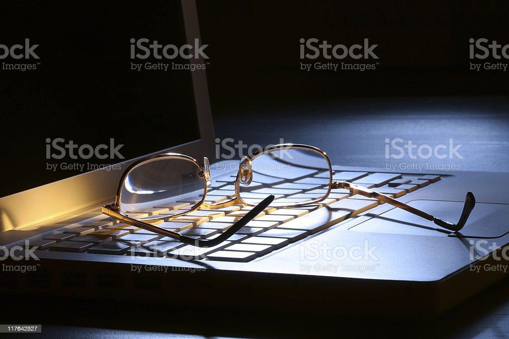 Golden glasses on laptop in moon light. Low Key scene. stock photo