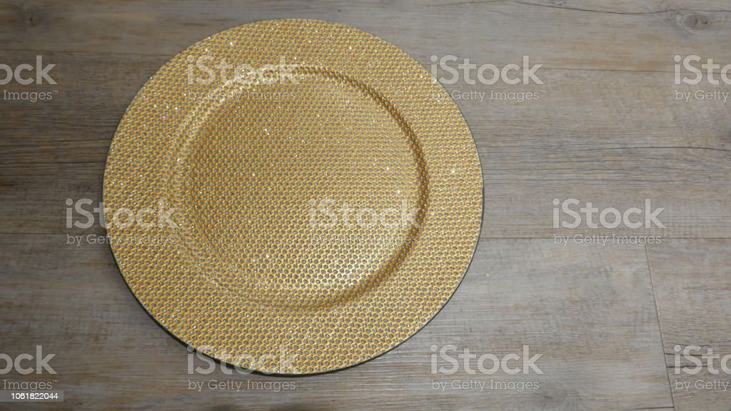 Golden glistening plate, isolated on wooden  background.Top view. stock photo