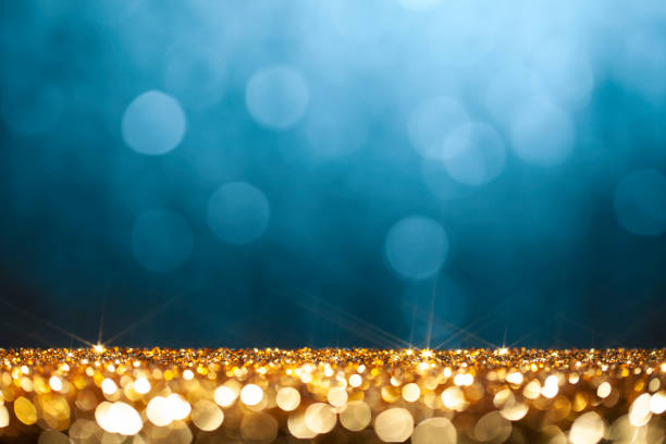 Golden glitter and blue defocused lights -  Christmas, Holiday, Celebration Background stock photo