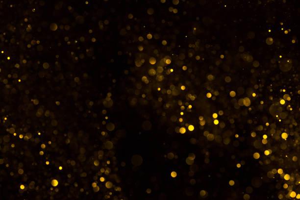 Golden glitter dust on black background