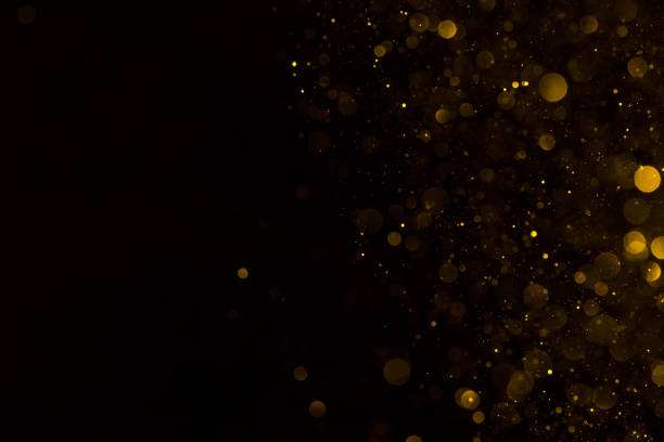 Golden glitter falling sparkle background Golden glitter falling sparkle background on black border composition glittering stock pictures, royalty-free photos & images