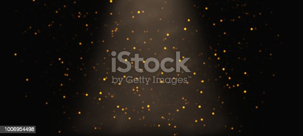 645451374istockphoto golden glitter falling through a cone of light in front of a black background - banner 1006954498
