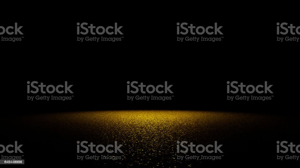 golden glitter on a flat surface lit by a bright spotlight stock photo