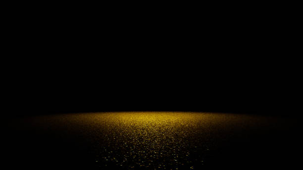 golden glitter on a flat surface lit by a bright spotlight - scintillante foto e immagini stock