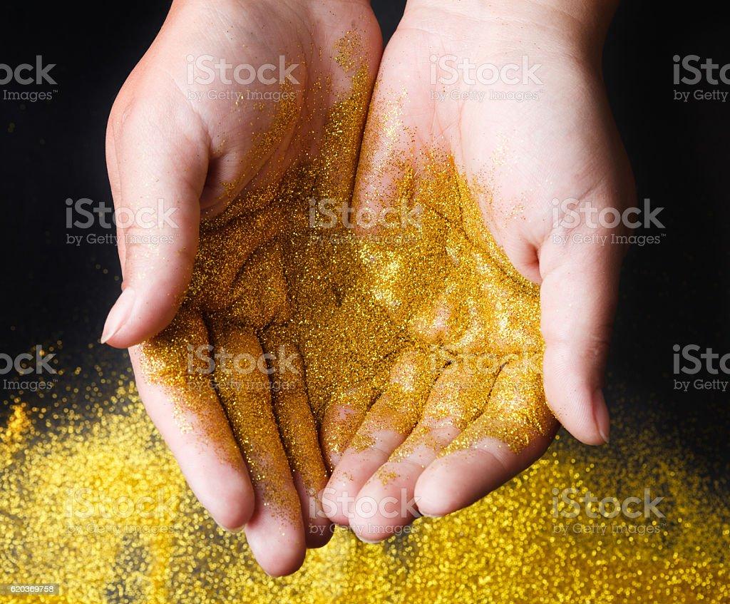Golden glitter sand in hands on black, abstract background. zbiór zdjęć royalty-free