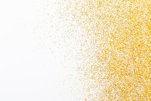 Golden glitter sand texture on white, abstract background. Yellow dusty shimmer decoration, shiny and sparkling frame, top view, copy space. Holidays and glamour concept.
