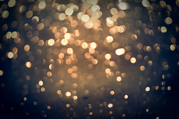 golden glittering bokeh background - low lighting stock photos and pictures