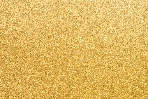 golden glittering paper background texture closeup