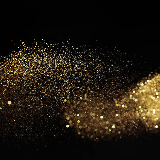 Golden glittery light on black background stock photo