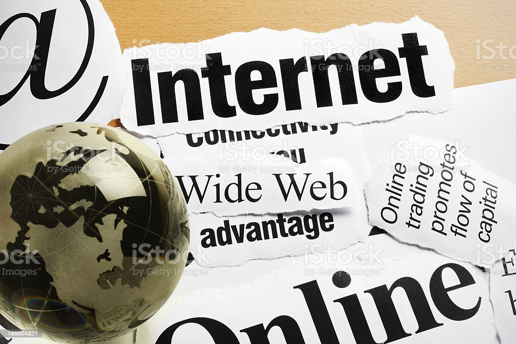 Golden globe paperweight on headlines concerning business and the internet royalty-free stock photo