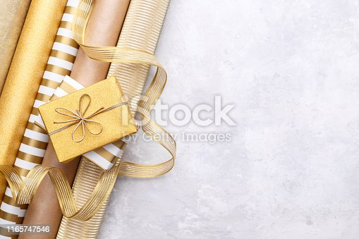 Golden glossy wrapping paper rolls, gift boxes and ribbons for hobby and crafts on grey stone background, close up with copy space