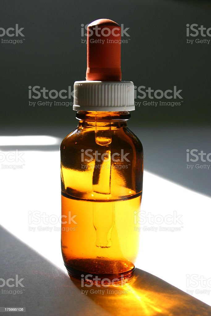 golden glowing tonic eye-dropper in the light royalty-free stock photo
