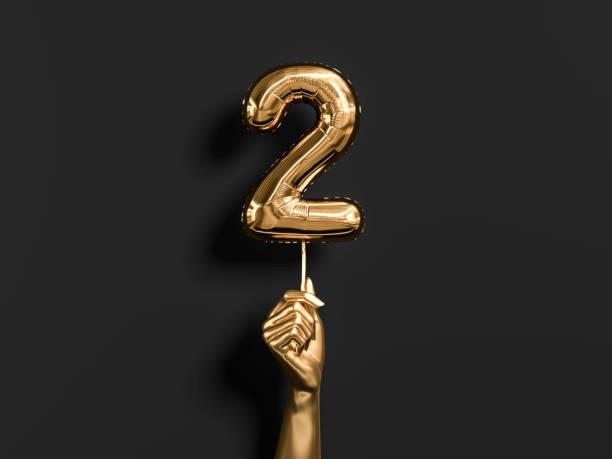 goldene hand hält nummer 2 folie ballon. zweijähriges jubiläum hintergrund. - 2 3 jahre stock-fotos und bilder