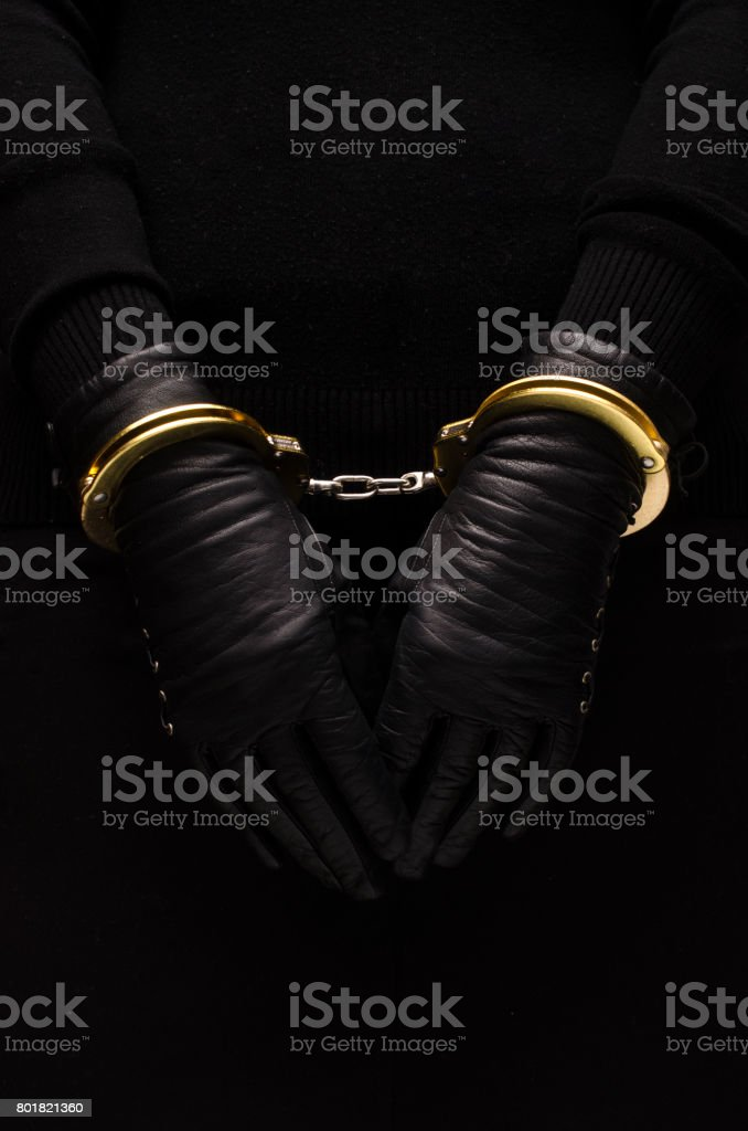 Golden handcuffs leather black gloves, concept Golden handcuffs leather black gloves, concept Arrest Stock Photo