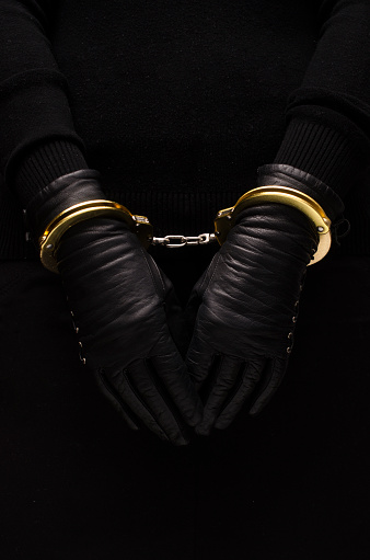 Golden Handcuffs Leather Black Gloves Concept Stock Photo - Download Image Now