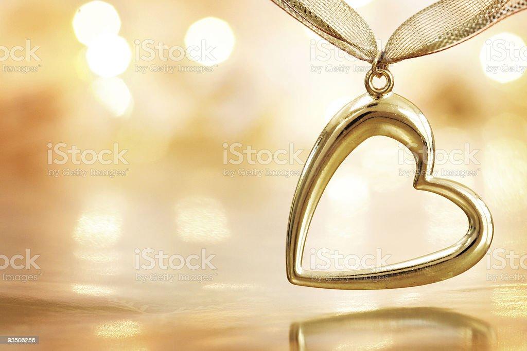 Golden heart on blazing defocused lights background stock photo