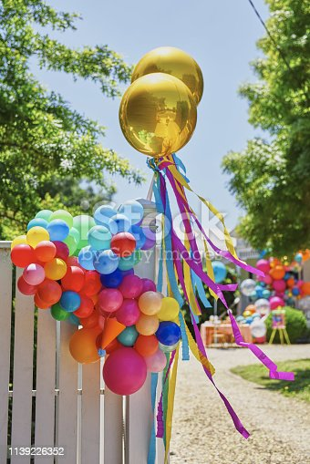 Golden helium balloons with ribbons and colourful balloon garland on white wooden fence on nature background. Birthday on open air concept.