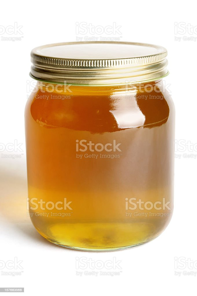 Golden honey in a single glass jar royalty-free stock photo