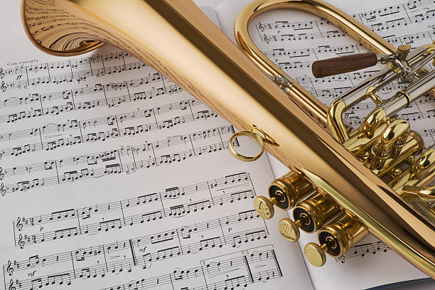Golden horn laying on sheet music stock photo