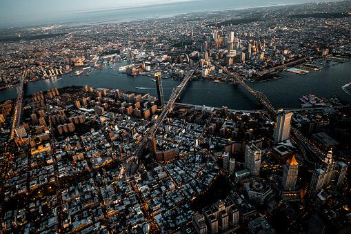 Brooklyn Bridge, Manhattan Bridge, and Williamsburg Bridge captured from air over the Lower Manhattan at dusk.