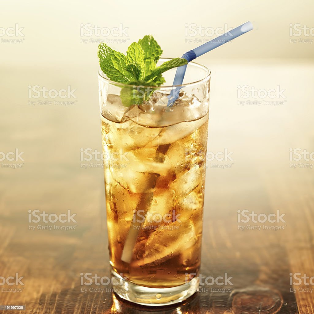 golden iced tea with blue straw and mint stock photo