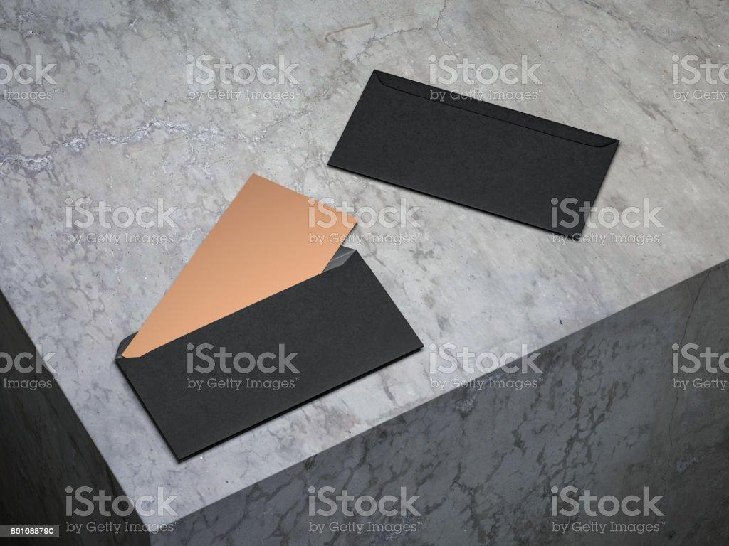 Golden invitation mockup in open black envelope on concrete floor stock photo