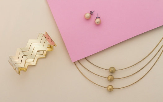 istock Golden jewelry set on pink and beige background 1127402029