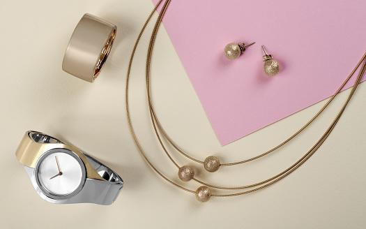 istock Golden jewelry set wrist watch on paper background 1063885990