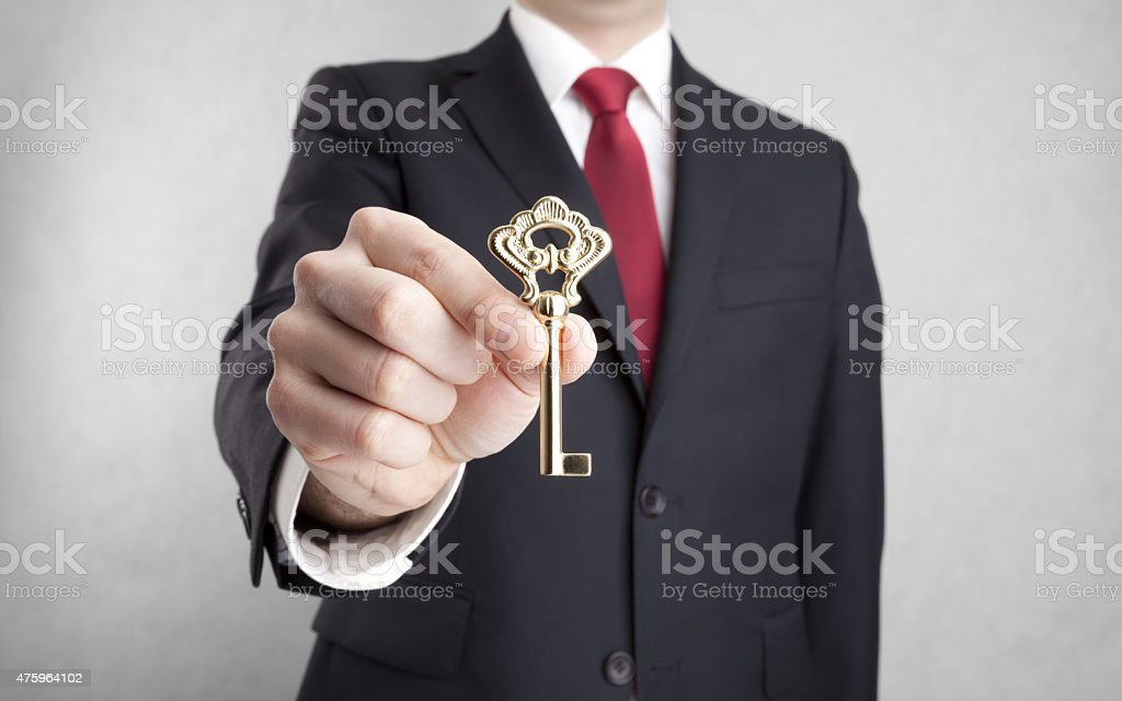 Golden key in businessman hand with clipping path stock photo