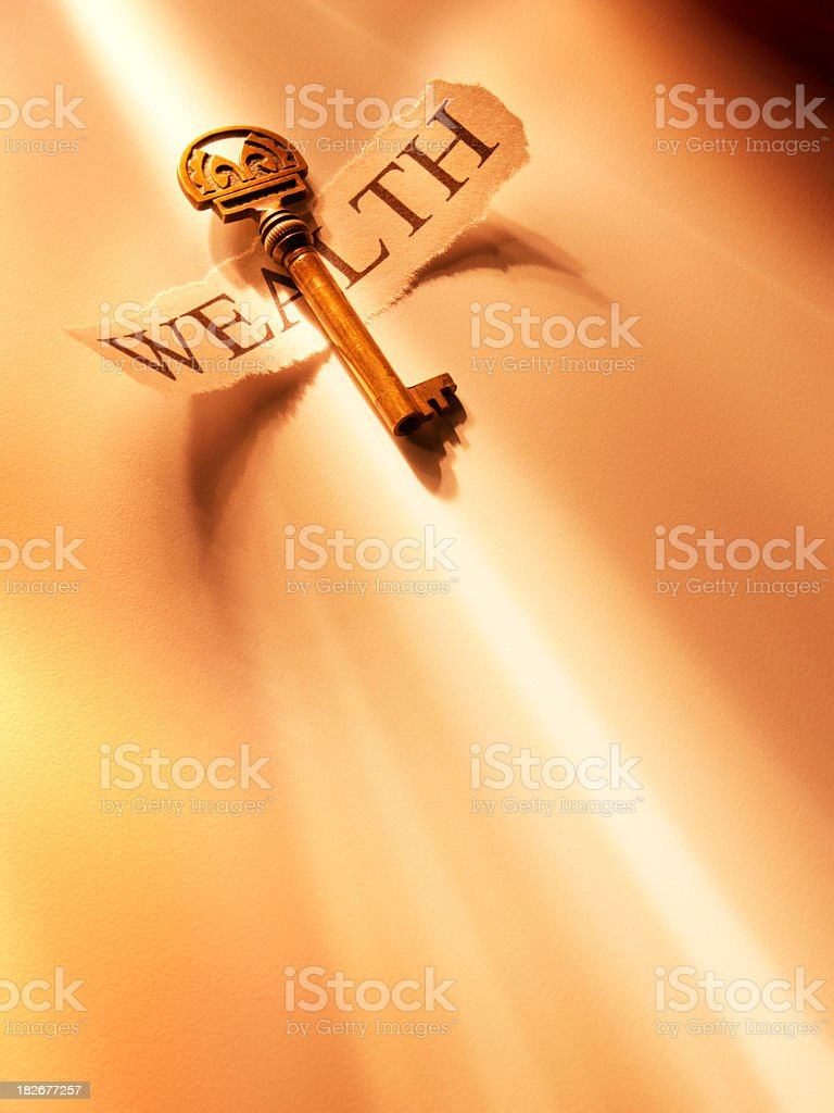 Golden key on torn paper printed  with word wealth royalty-free stock photo