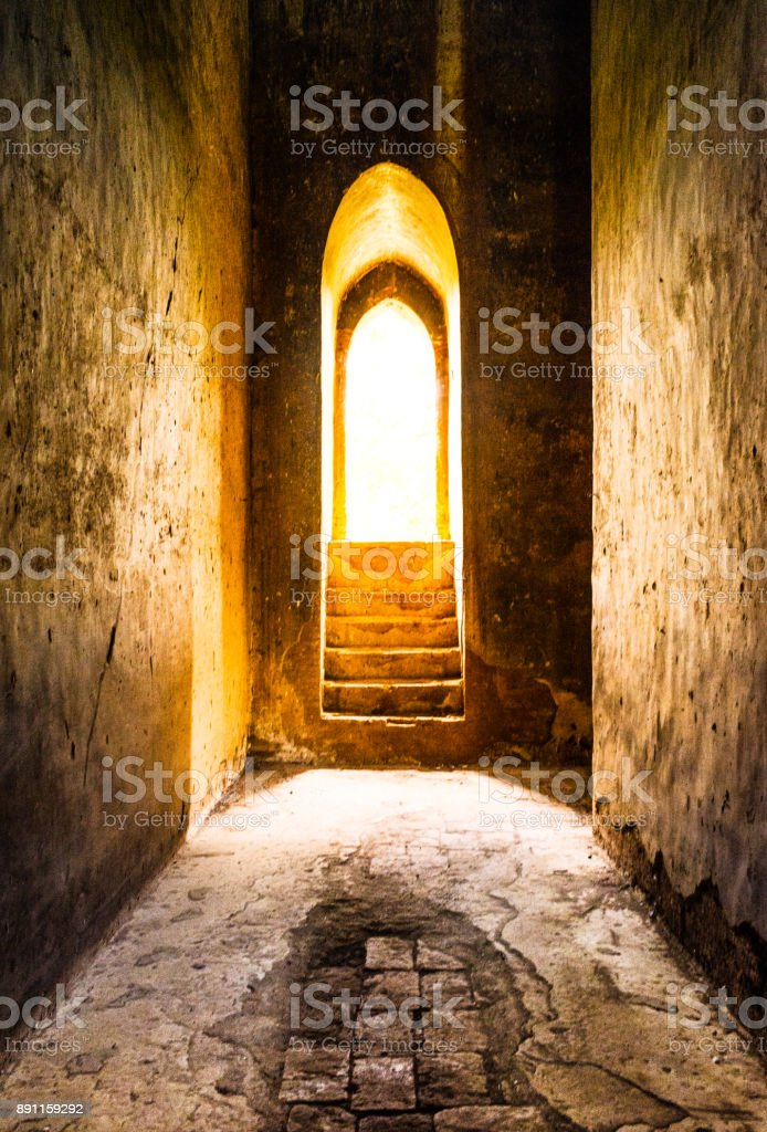 Golden light at the end of the tunnel concept - view of a temple door with light shining through stock photo